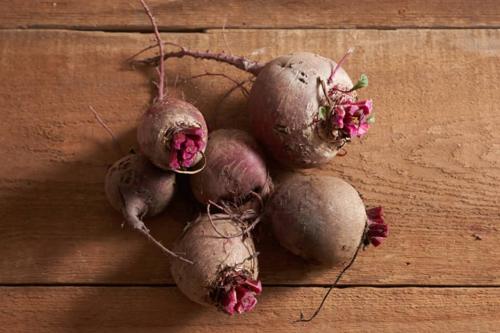 Six fresh trimmed beets on a wooden surface.