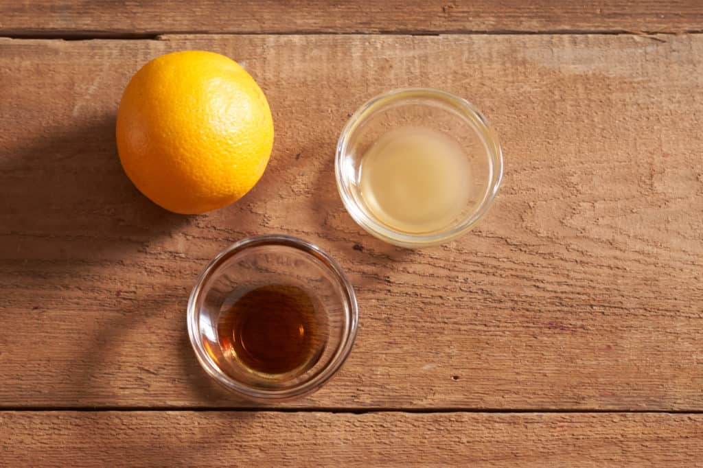 A fresh orange, and two small glass bowls with maple syrup and cider vinegar.