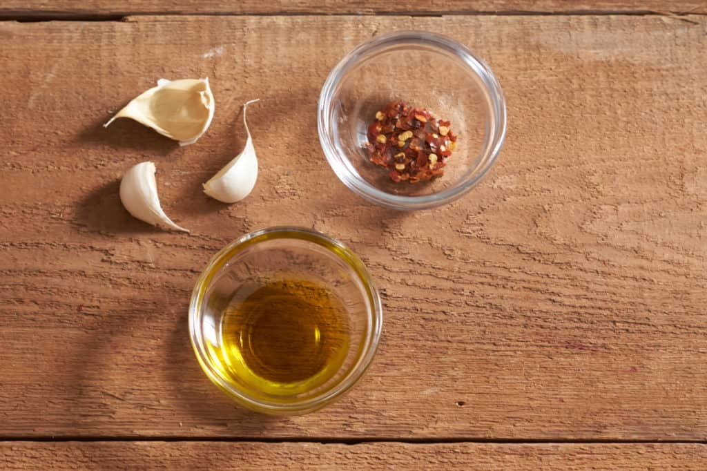 Three cloves of garlic and two small glass bowls with olive oil and crushed red pepper.