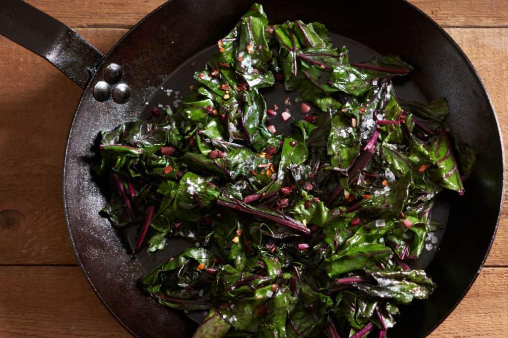 Sautéed beet greens in a cast iron skillet.