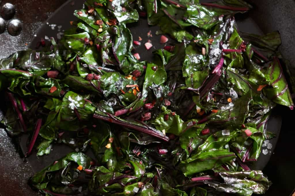 Sautéed beet greens in a cast iron skillet.