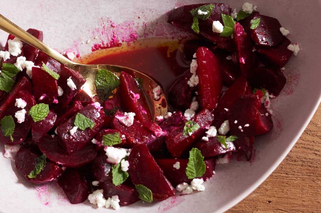 A gold spoon sits in a pink bowl full of oven-roasted beets with goat cheese, orange vinaigrette, and mint.
