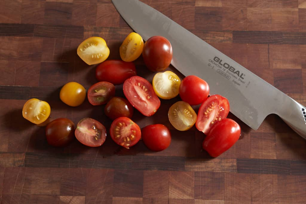 Sliced red and yellow cherry tomatoes on a cutting board with a chef's knife.