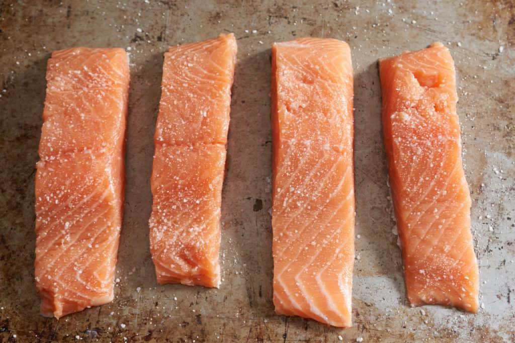 Four filets of raw salmon seasoned with salt on a baking sheet.