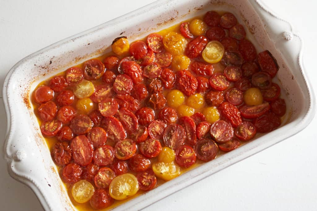 Roasted cherry tomatoes in a white casserole dish.