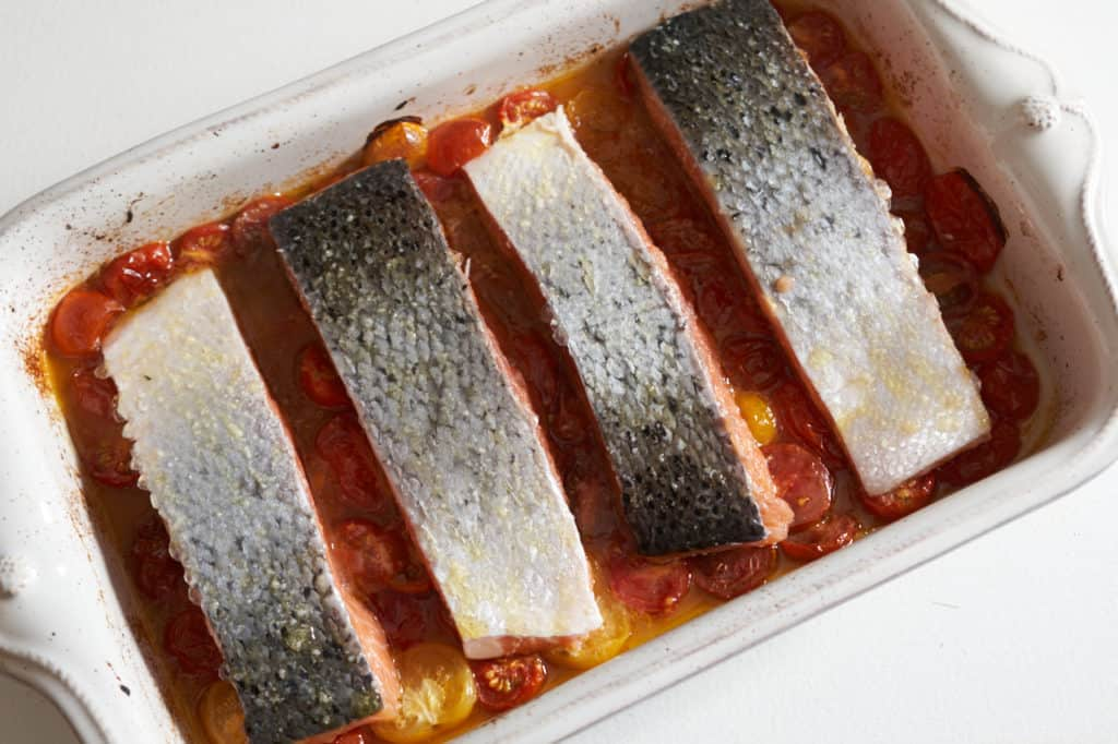 Raw salmon filets on top of roasted tomatoes in a casserole dish.