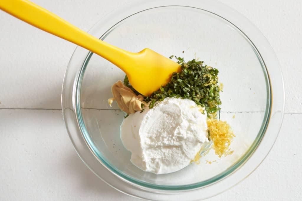 A yellow spatula in a glass bowl with yogurt, basil, mustard, and lemon zest.