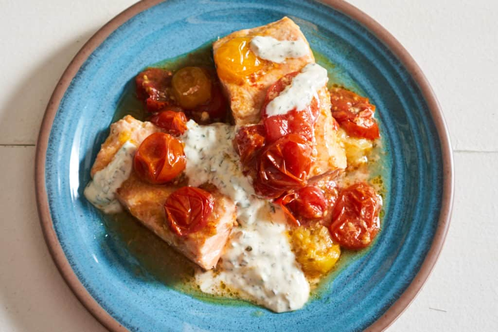 Oven baked salmon with roasted tomatoes and basil yogurt sauce on a blue plate.
