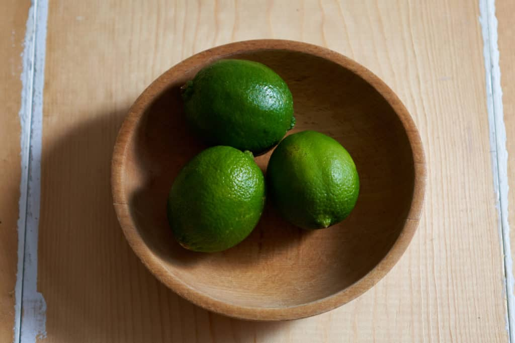 Three limes in a wooden bowl.