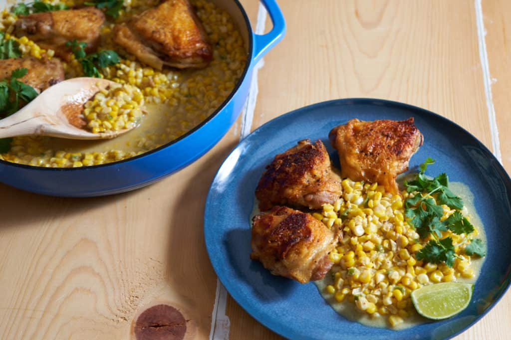 Chicken thighs with coconut milk creamed corn on a blue plate garnished with lime and cilantro, next to a blue casserole pan with more chicken and corn.