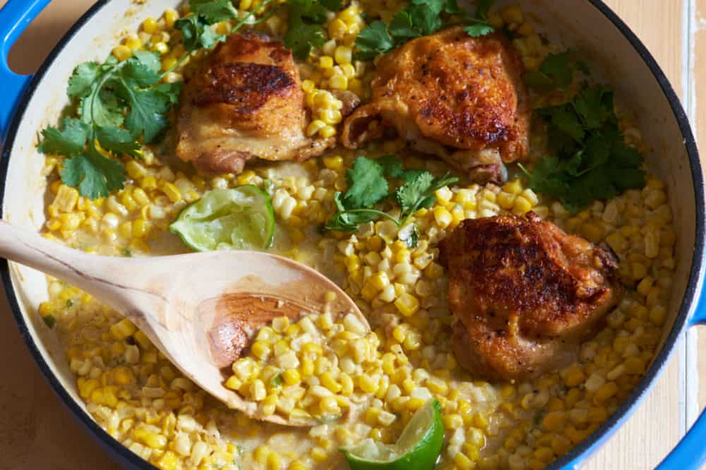 A wooden spoon in a pan of chicken thighs with coconut milk creamed corn, garnished with cilantro and lime wedges.