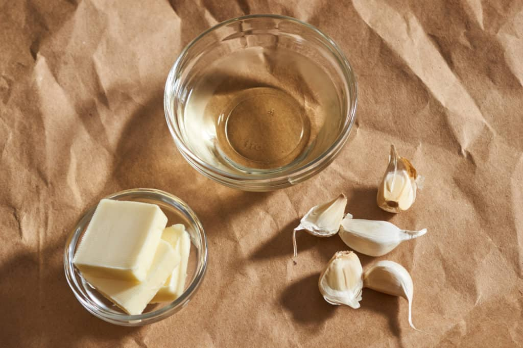 Butter, a small bowl of white wine, and some garlic cloves.