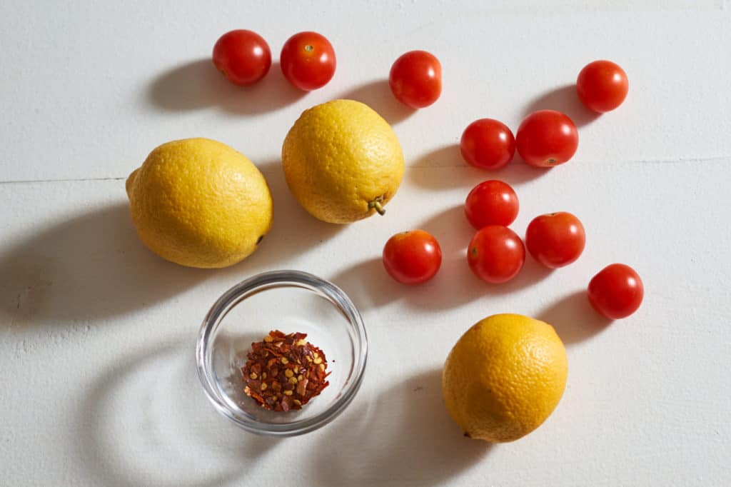 Lemons, cherry tomatoes, and a small bowl of crushed red pepper.