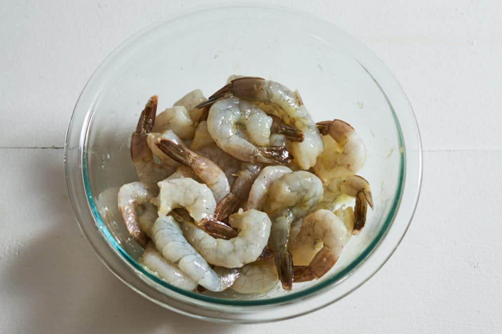 A glass bowl filled with raw shrimp marinating in olive oil and garlic.
