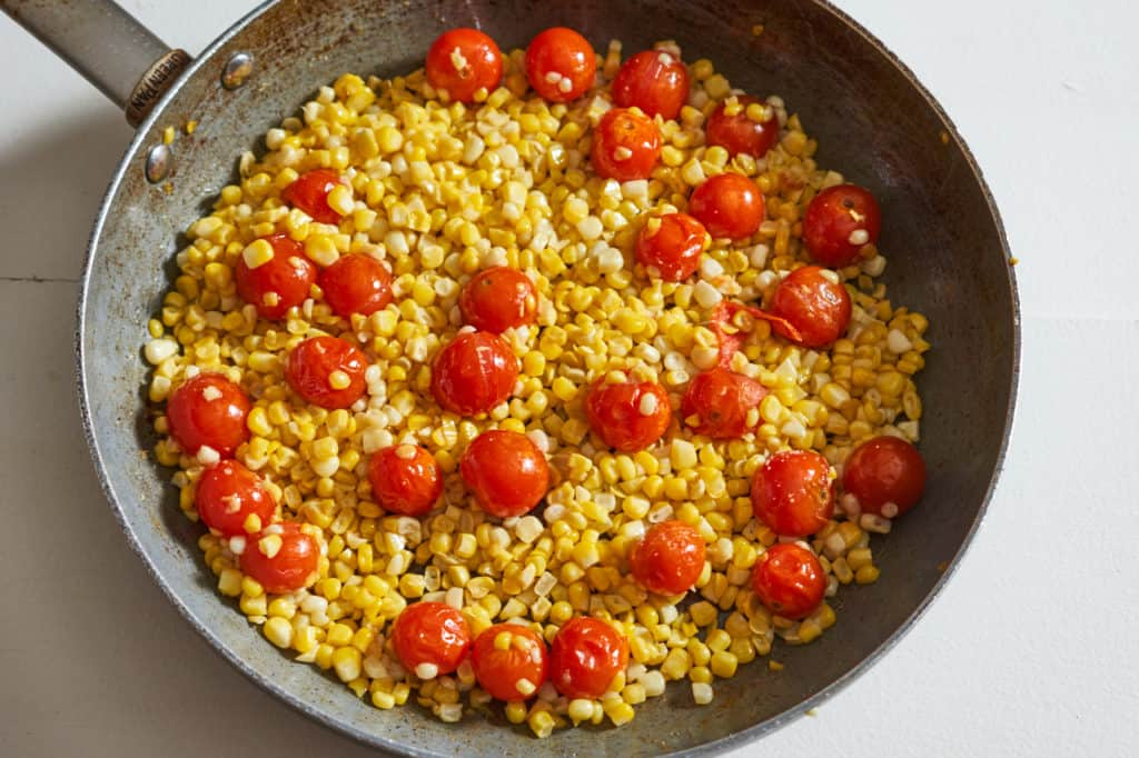 Corn and cherry tomatoes in a large skillet.