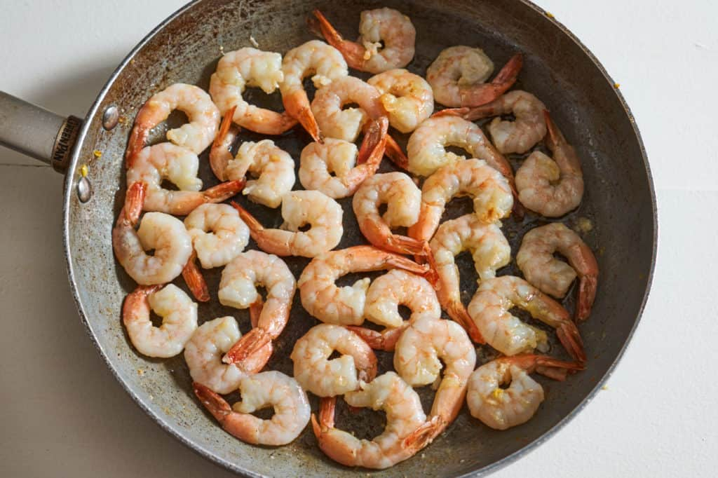 Cooked shrimp in a skillet.