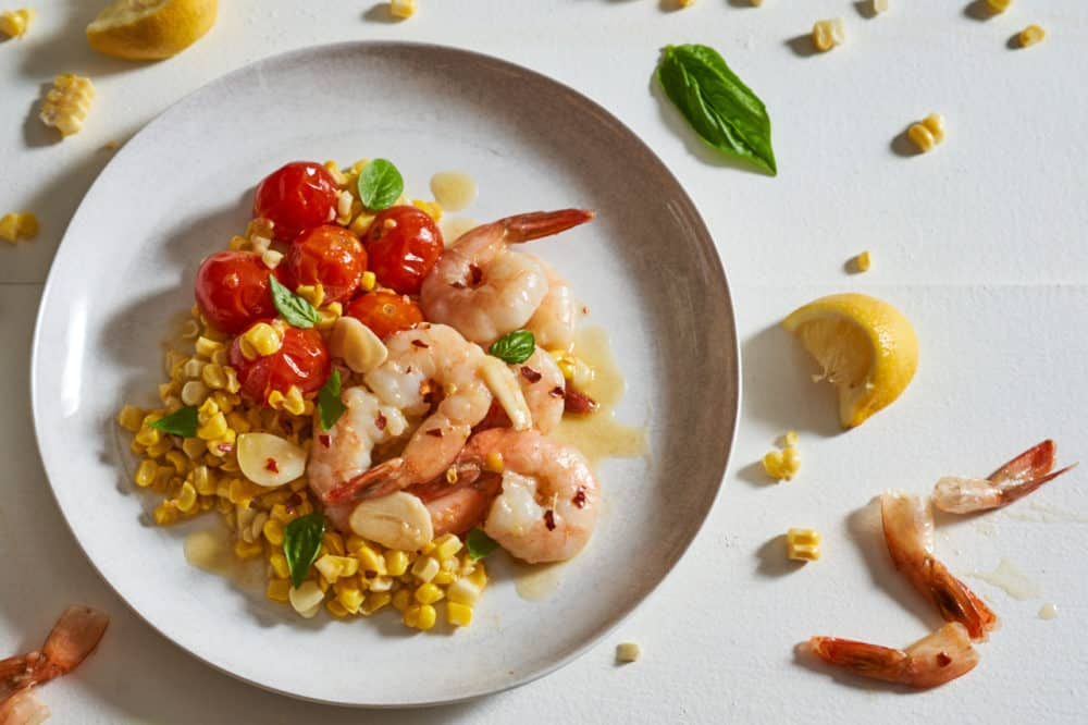 A plate of shrimp scampi with tomatoes and corn surrounded by corn kernels, shrimp tails and basil leaves.