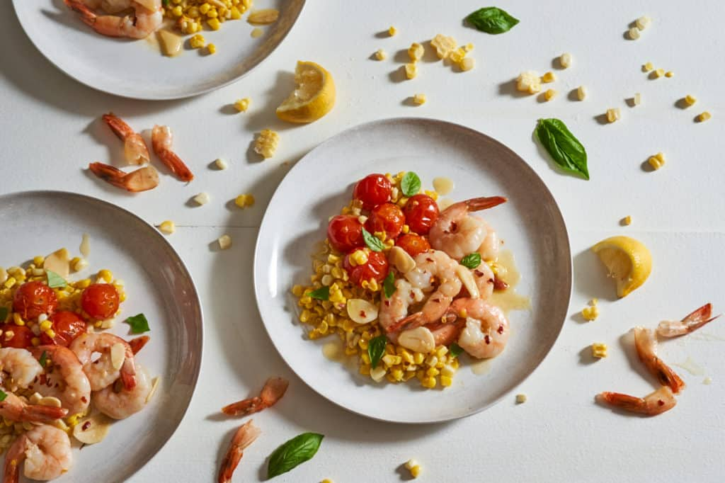 Plates of shrimp scampi with tomatoes and corn surrounded by corn kernels, shrimp tails and basil leaves.