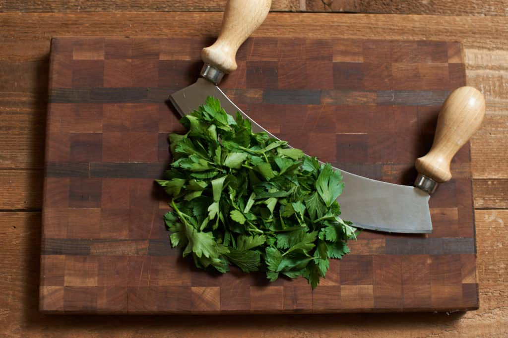 A mezzaluna with chopped parsley on a cutting board.