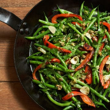 Fresh green bean salad with red peppers, capers and herbs in a cast iron skillet.