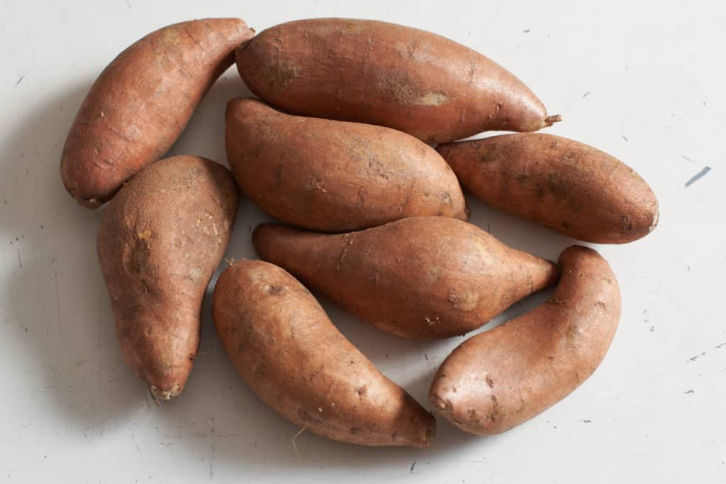 Whole sweet potatoes on a white surface.