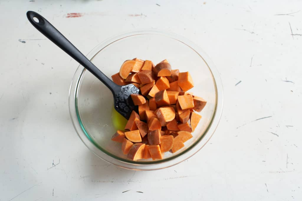 A spatula sits in a glass bowl filled with diced sweet potatoes.