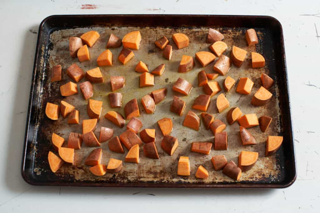 Diced sweet potatoes coated in olive oil on a baking sheet.