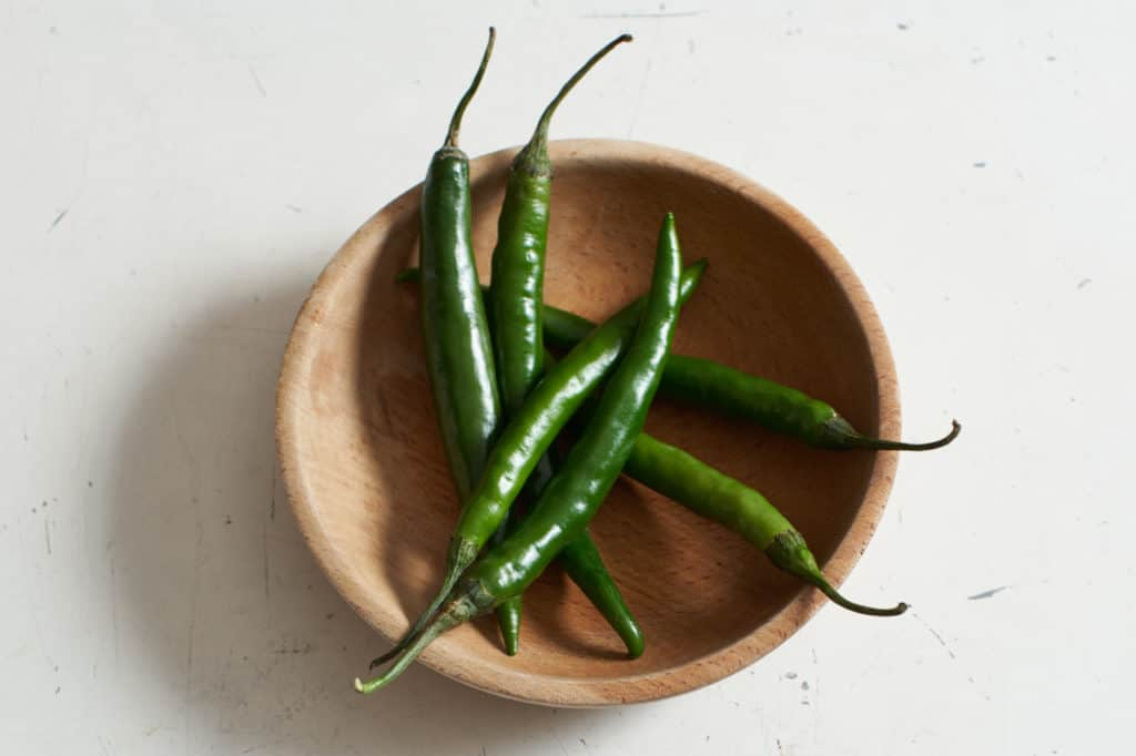Green chiles in a wooden bowl.