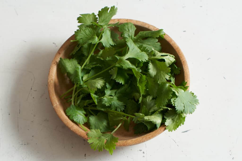 Fresh cilantro in a wooden bowl.