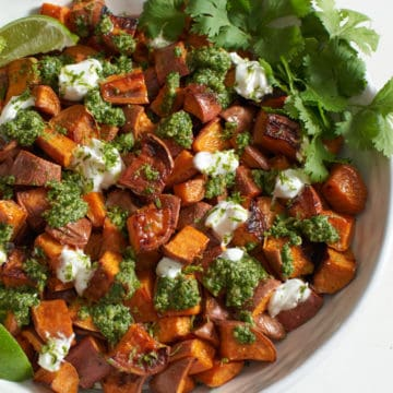 Oven roasted sweet potatoes with chile lime cilantro sauce in a white bowl.
