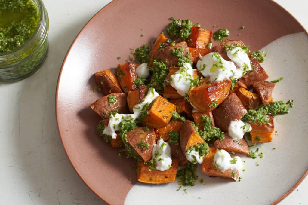 Oven roasted sweet potatoes with chile lime cilantro sauce on a brown and white plate.