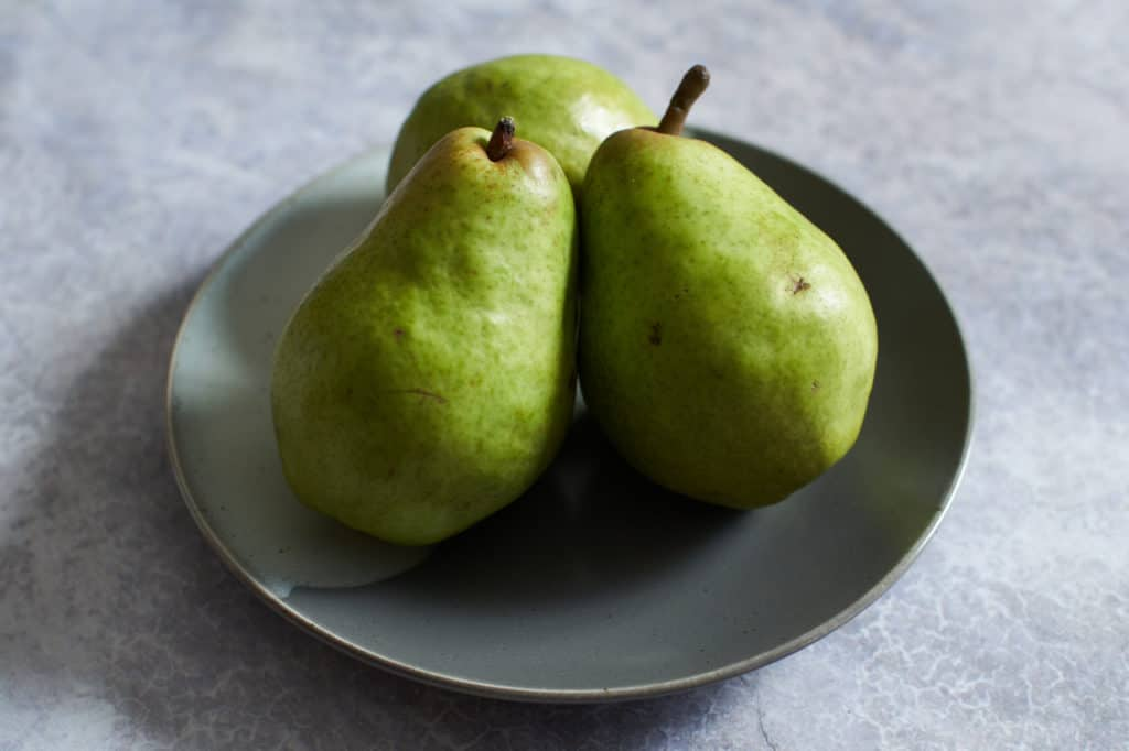 Three pears on a gray plate.