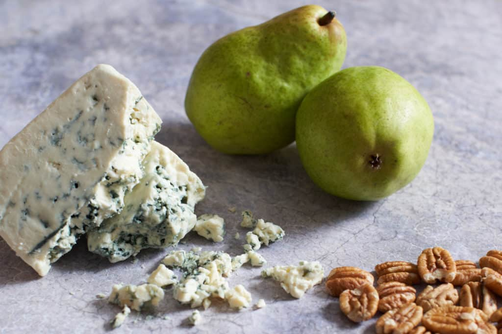 Two pears, some blue cheese wedges and pecans on a gray surface.