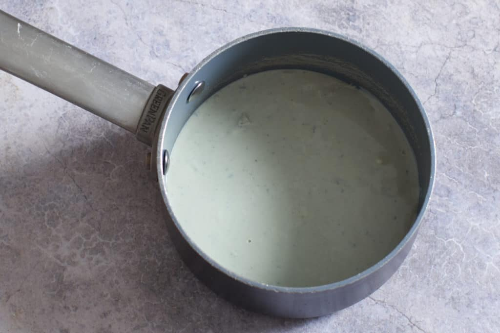 A sauce pan with melted blue cheese and cream.