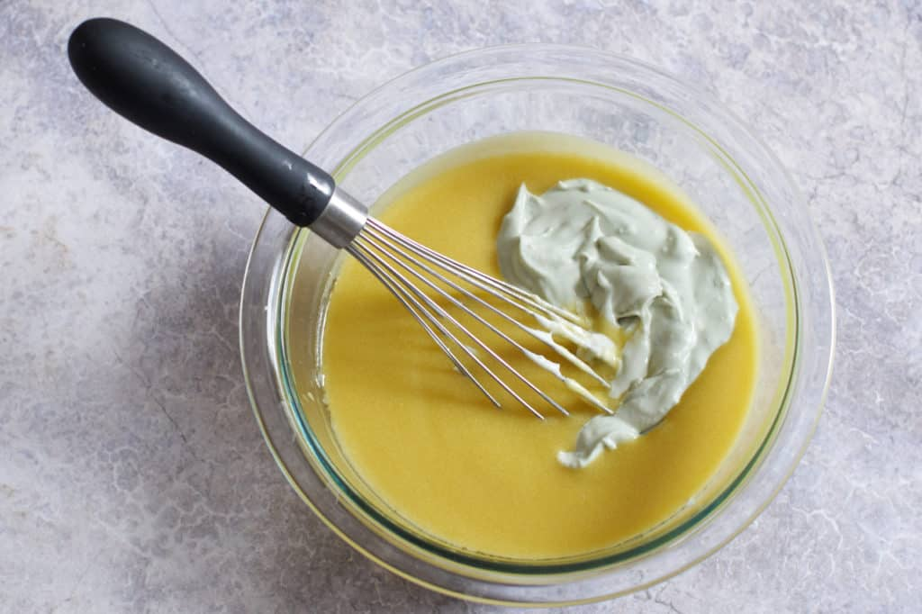 A whisk in a bowl of dijon vinaigrette with blue cheese dressing base added.