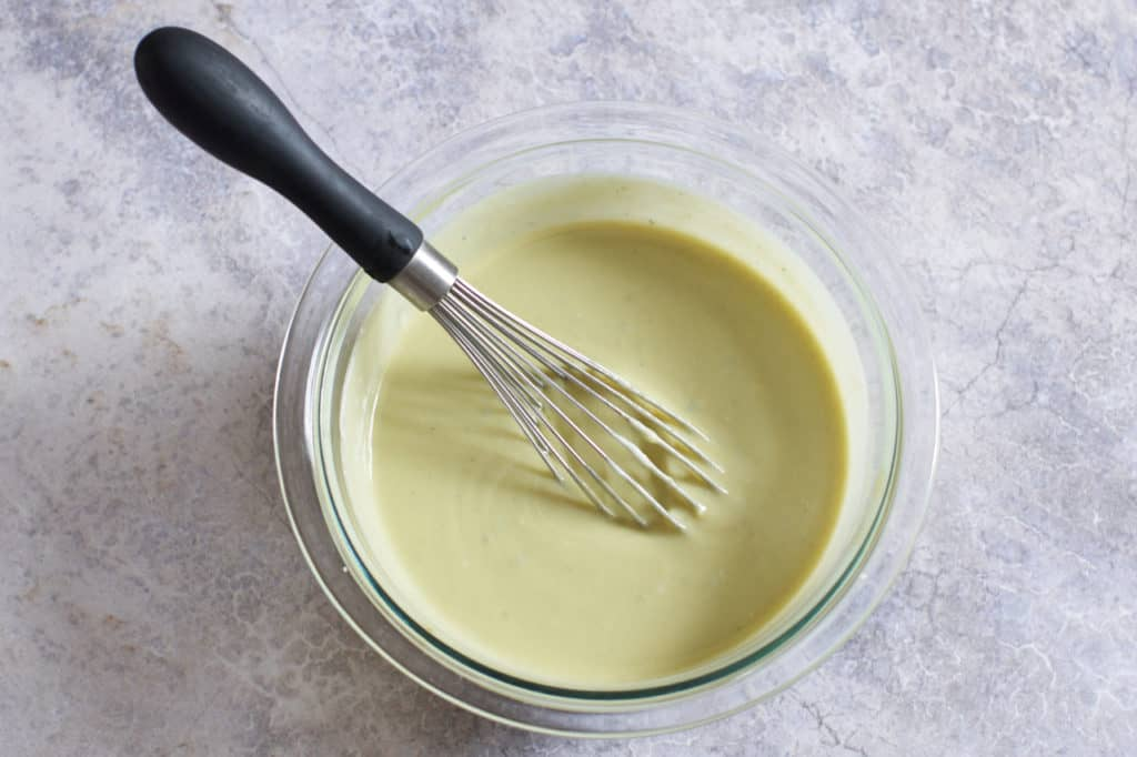 A whisk in a bowl of blue cheese vinaigrette.