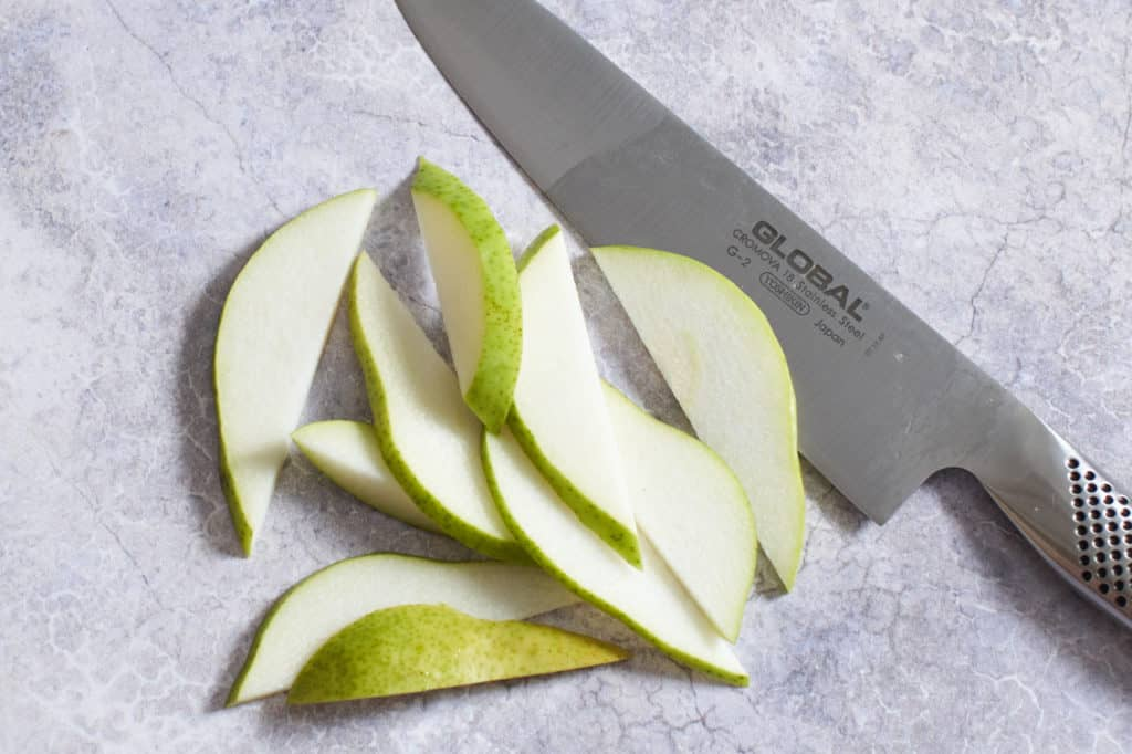 Sliced pears next to a chef's knife.