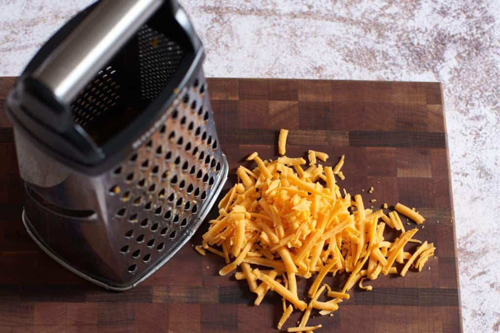 A box grater and grated cheddar cheese on a cutting board.