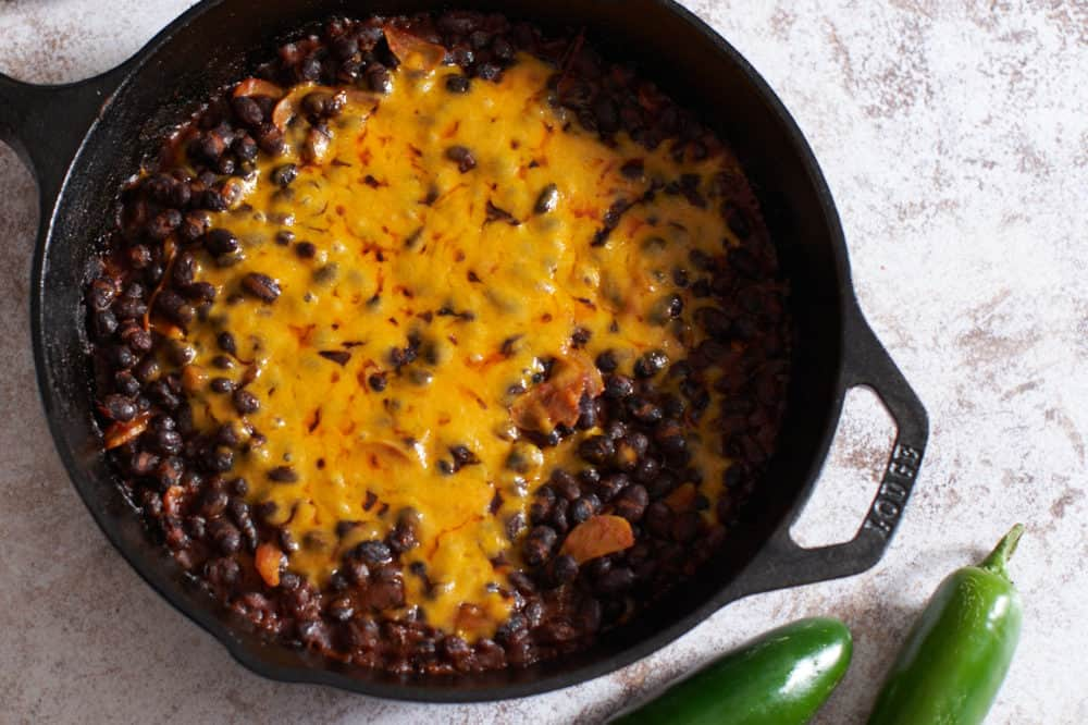 Spicy black beans with melted cheddar cheese in a cast iron skillet.