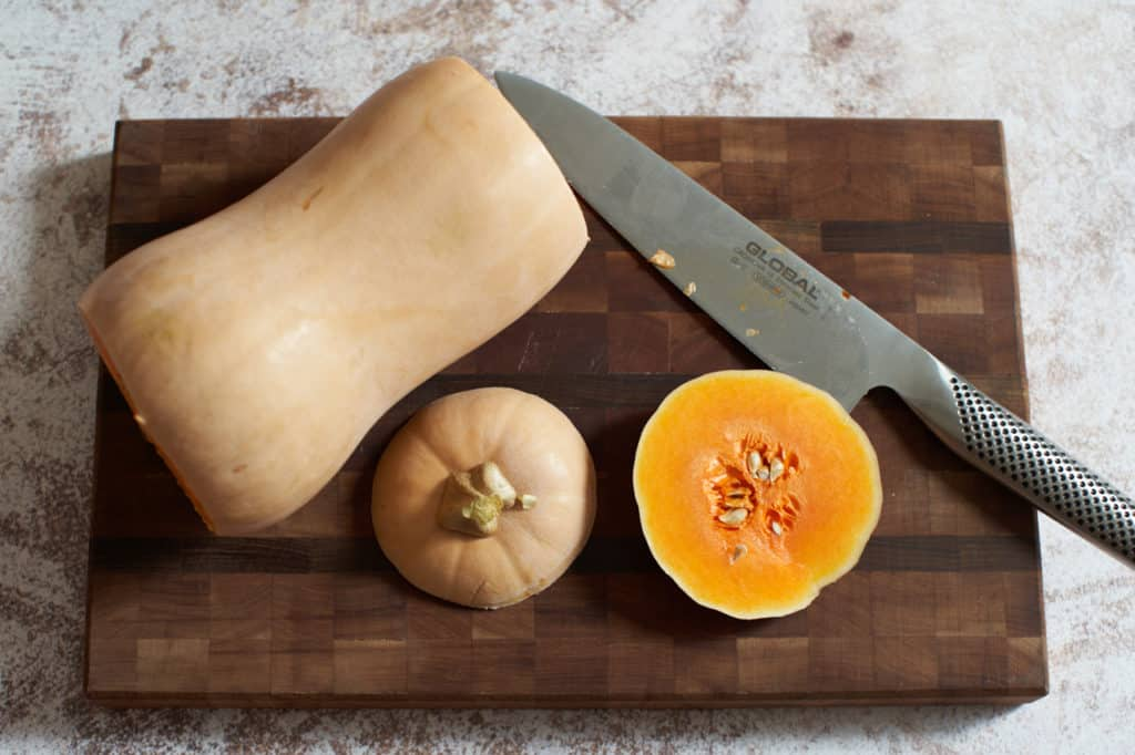 A butternut squash with the top and bottom cut off on a cutting board.