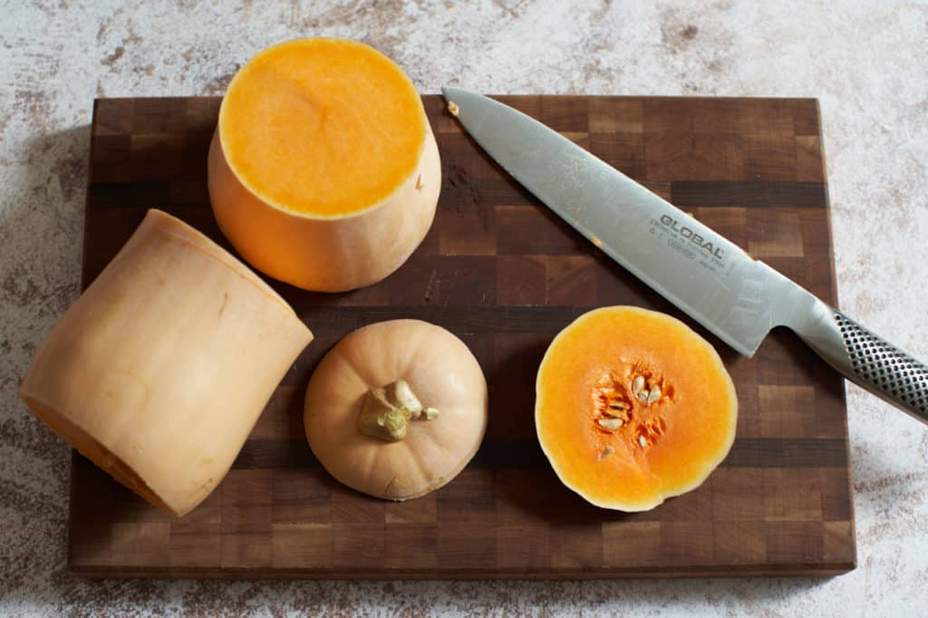 A butternut squash cut in half with the top and bottom cut off on a cutting board.