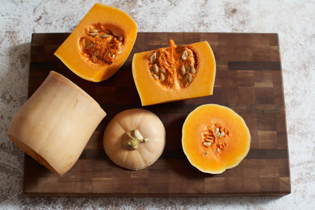 A butternut squash cut into pieces on a cutting board.
