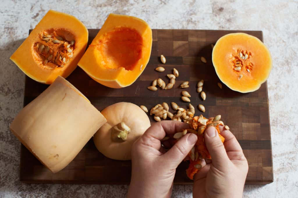 A woman's hands are shown separating butternut squash seeds from its pulp.