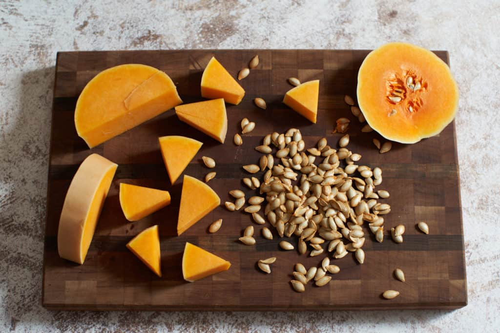 A butternut squash cut into pieces on a cutting board along with its seeds.