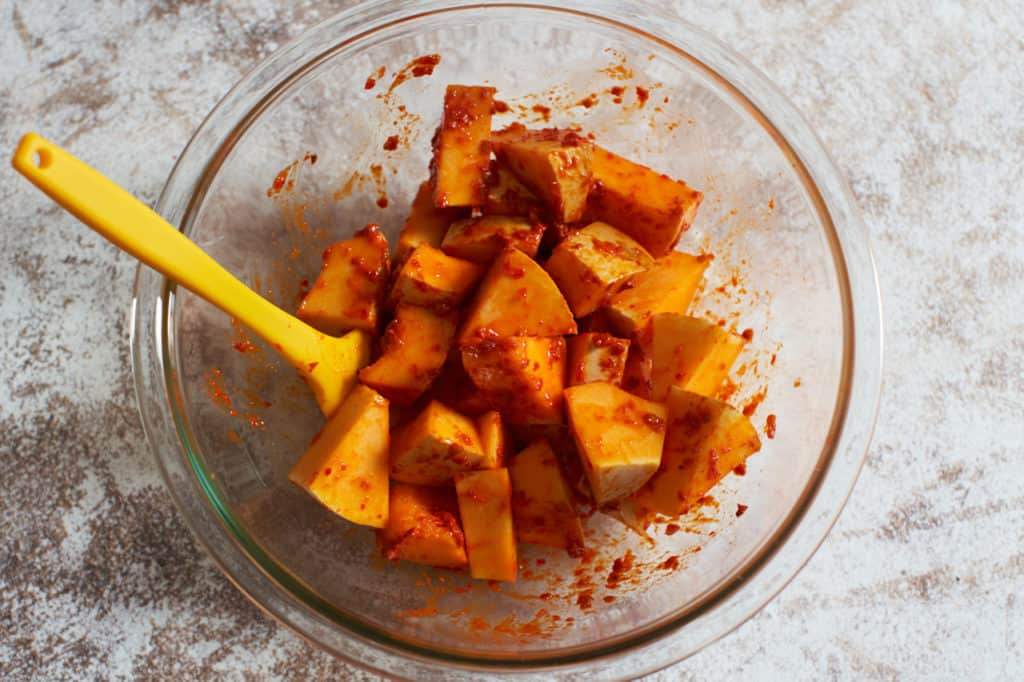 A glass bowl containing chopped butternut squash mixed with harissa.