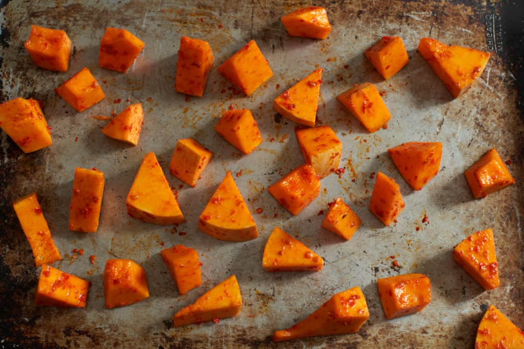 Butternut squash coated in harissa ready to be baked.