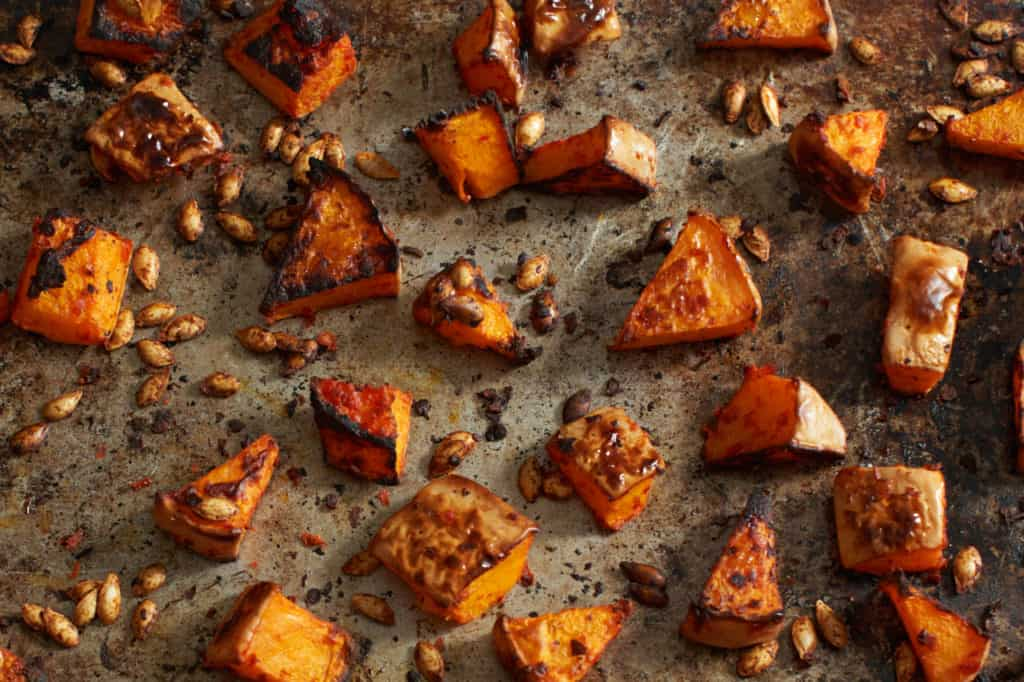 Roasted butternut squash and seeds on a baking sheet.
