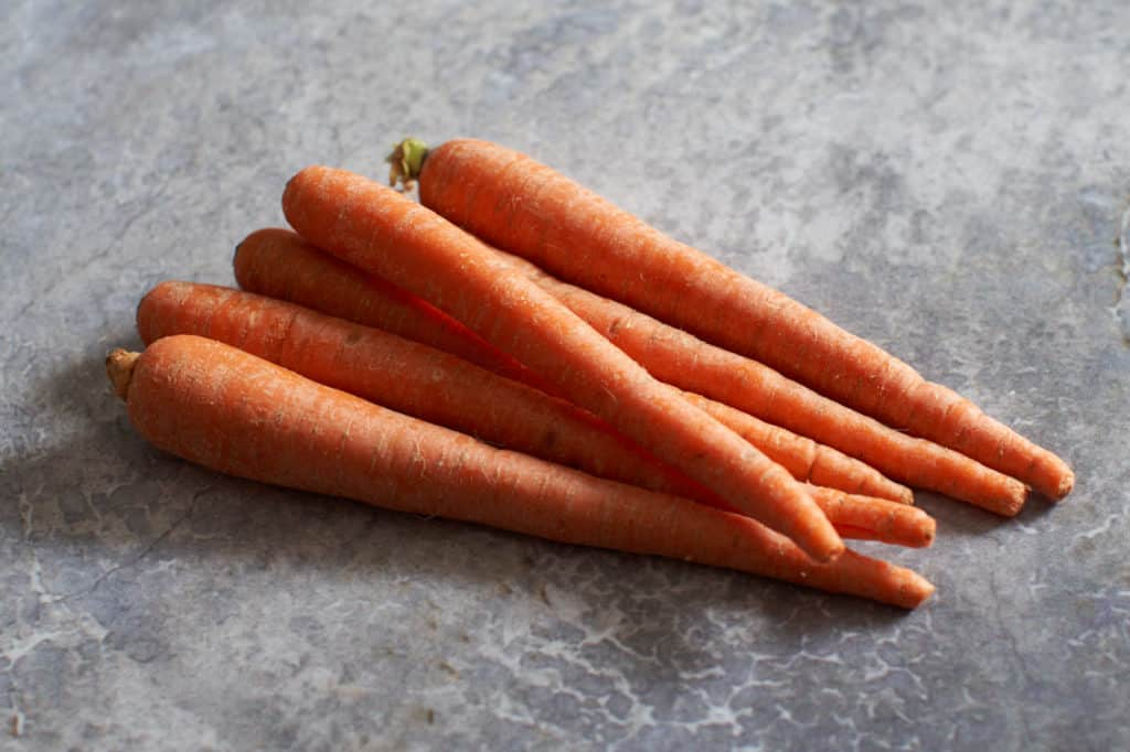 Whole carrots on a gray surface.