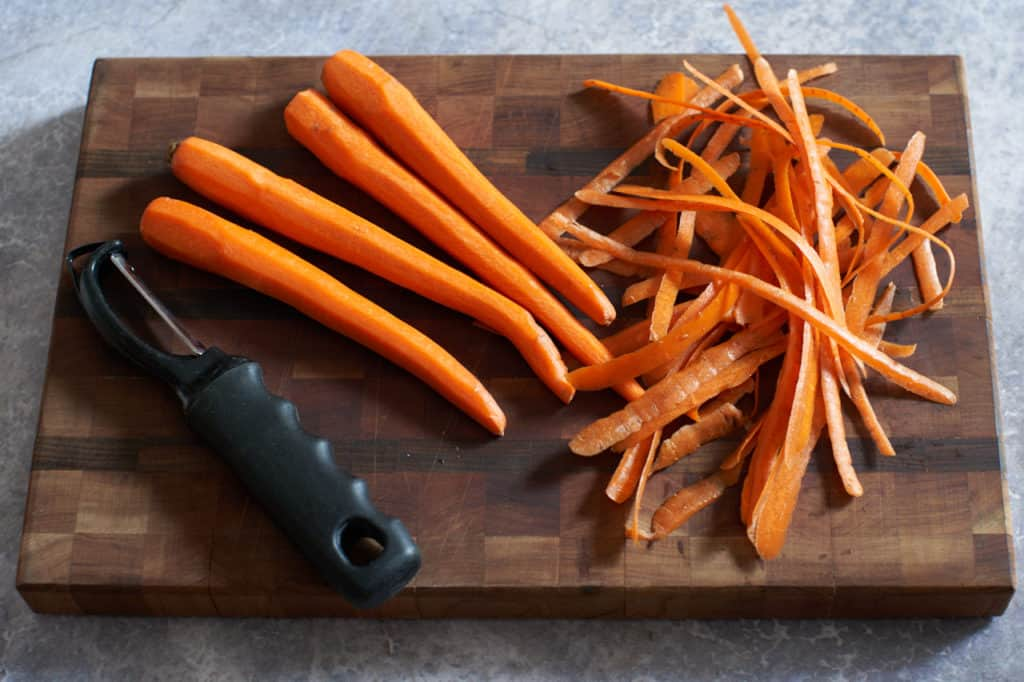 Peeled carrots with a peeler on a wooden cutting board.