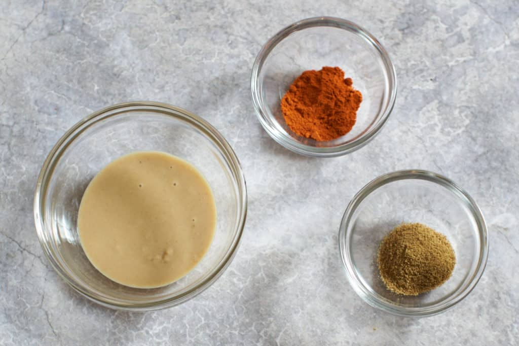 Three small glass bowls filled with tahini, cayenne pepper and cumin.